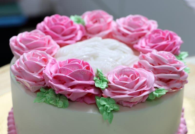 Rosa Rosen und gr?nes Blatt der Buttercreme auf dem wei?en Kuchen stockbild
