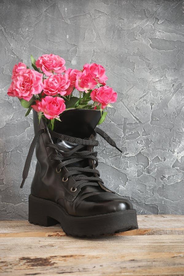 Rosa Rosenschläuche in schwarzem Kampfstiefel lizenzfreie stockfotografie