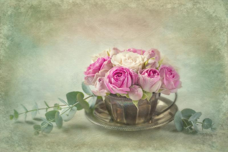 Rosa rosor i en tekopp arkivfoto