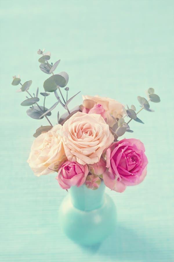 Rosa rosor i en tekopp royaltyfri bild