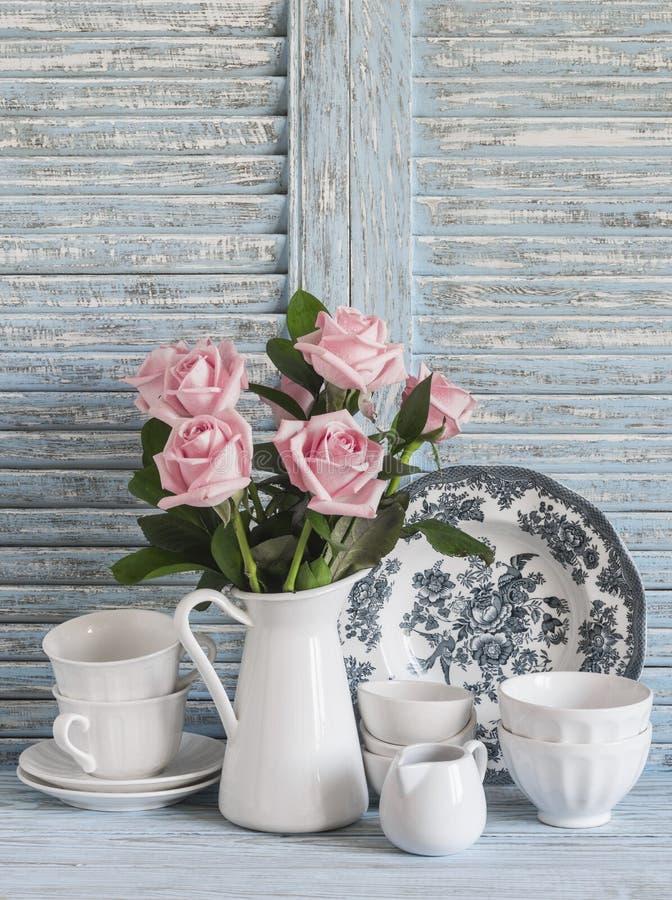 Rosa rosor i en vit emaljerad kanna, tappninglerkärl på blå trälantlig bakgrund Kökstilleben i tappningstil royaltyfria foton