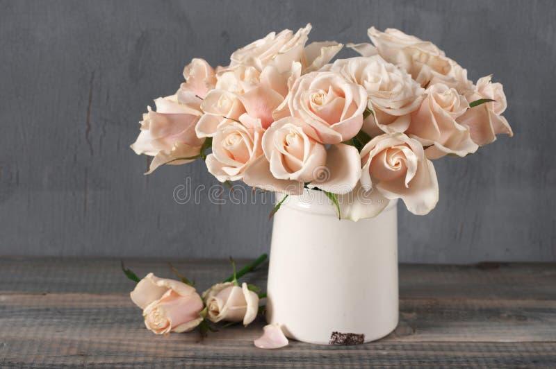 Rosa rosor i tappningvas arkivbild