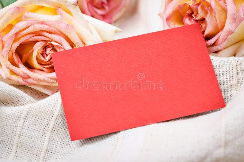 Rosa rosor med det tomma röda gåvakortet royaltyfria bilder