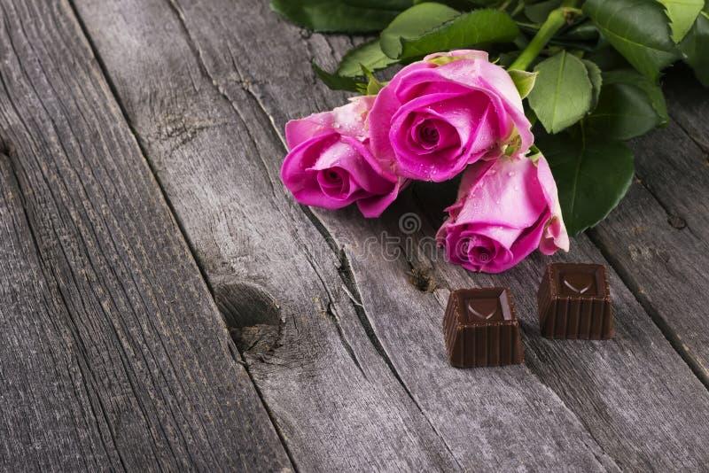 Rosa rosor och choklader i form av hjärta mot en mörk backgr arkivfoto