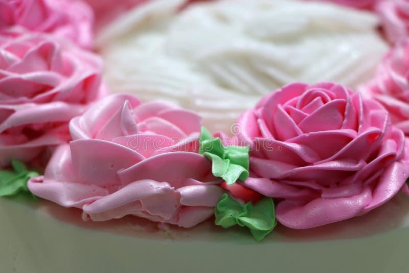 Rosa rosor och gr?nt blad av sm?rkr?m p? den vita kakan arkivfoto