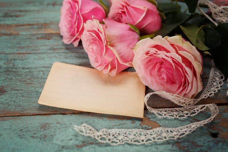 Rosa rosor på en trätabell. Tappning arkivbild