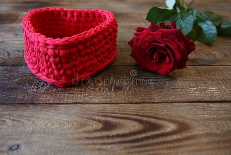 Rosa rossa con le gocce di acqua e cuore rosso per un regalo su un fondo di legno con lo spazio della copia per testo immagini stock libere da diritti