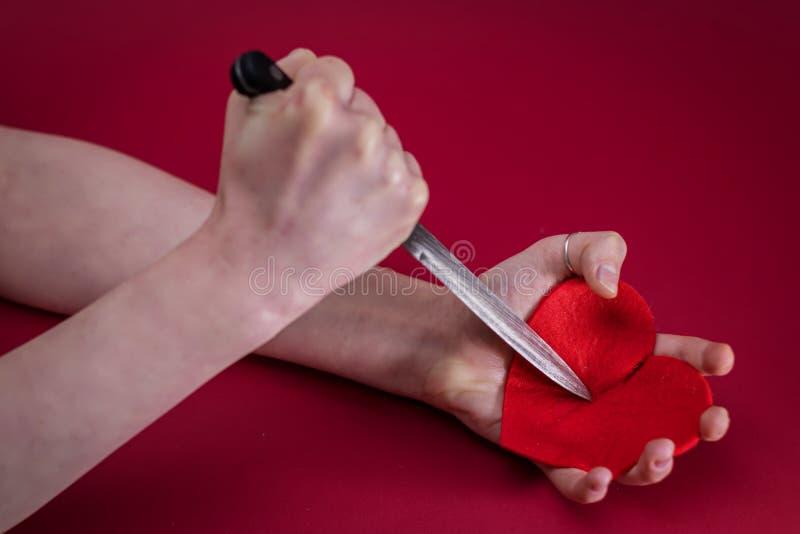 Rosa rossa Cuori rossi Breakheart Femminile passilo e perfora coltello del cuore fotografie stock libere da diritti