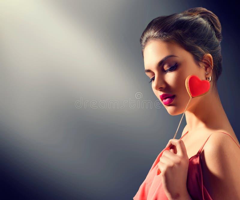 Rosa rossa La giovane ragazza di modello di bellezza con il cuore del biglietto di S. Valentino ha modellato il biscotto immagine stock