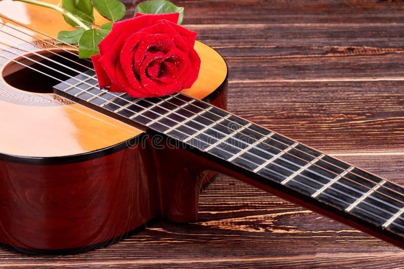 Rosa rossa sulla chitarra acustica fotografia stock