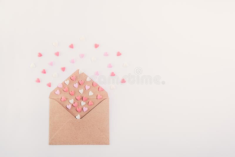 Rosa, rote und weiße Bonbonzuckersüßigkeitsherzen fliegen aus Kraftpapierumschlag auf dem weißen Hintergrund heraus getrennt auf  stockfoto