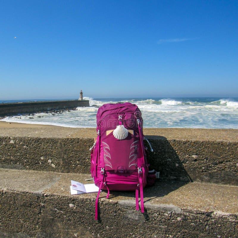 Rosa Rucksack mit Muschelschalesymbol des Pilgers an der Betonmauer mit Ozean mit enormen weißen Wellen und am blauen Himmel auf  stockfoto