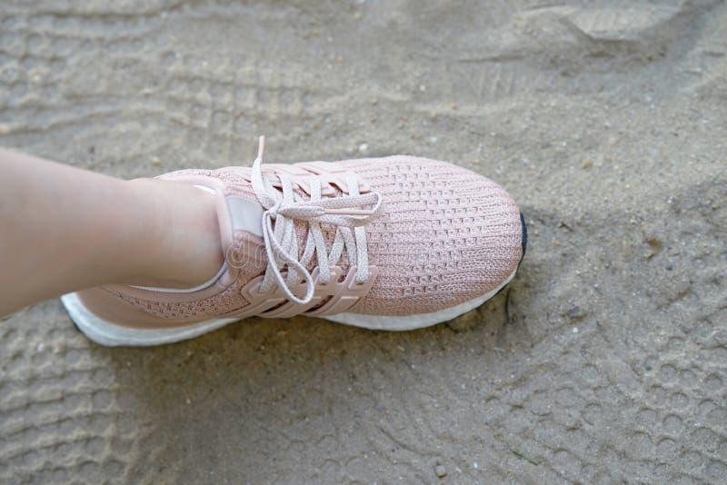 Rosa runnung skor en sidostämpel på sand med skotryck royaltyfria foton
