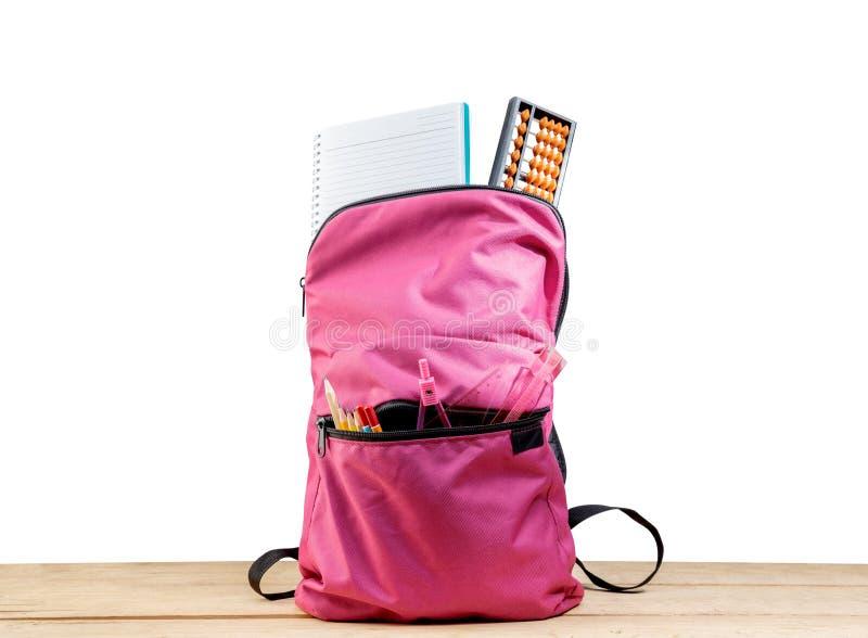 Rosa ryggsäck med boken och olik brevpapper på trätabellen arkivfoton