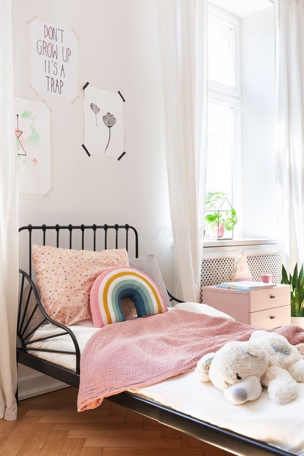 Rosa sängkläder- och nallebjörn på liten ungesäng royaltyfri fotografi