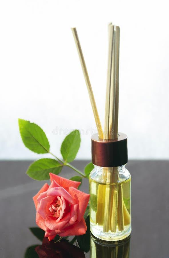 Rosa scented a garrafa de óleo com varas de madeira fotos de stock royalty free