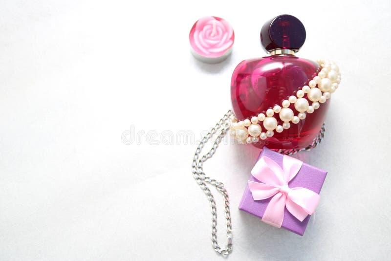 Rosa schöne transparente Glasflasche weibliches Parfüm verziert mit weißen Perlen und eine Kerze in Form eines Rose blauen smal stockbilder