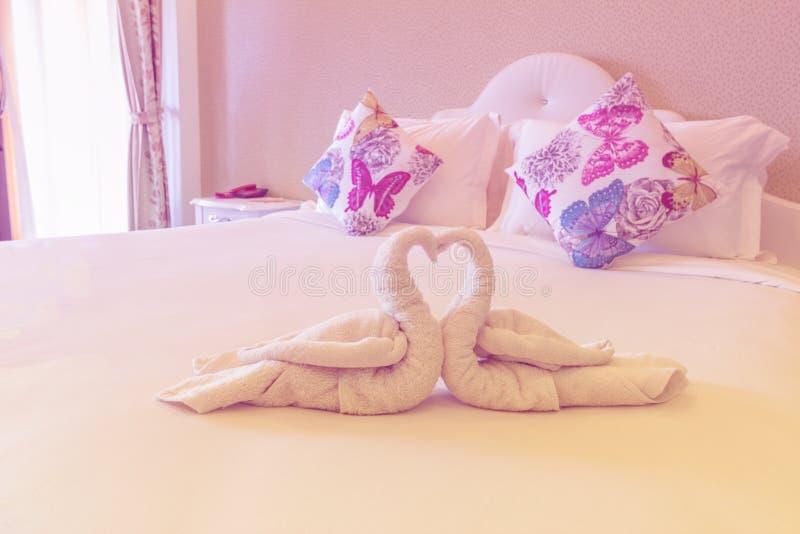 Rosa Schlafzimmer mit gefaltetem Tuch in der Schwanform auf Bett bereiten sich für vor stockfoto
