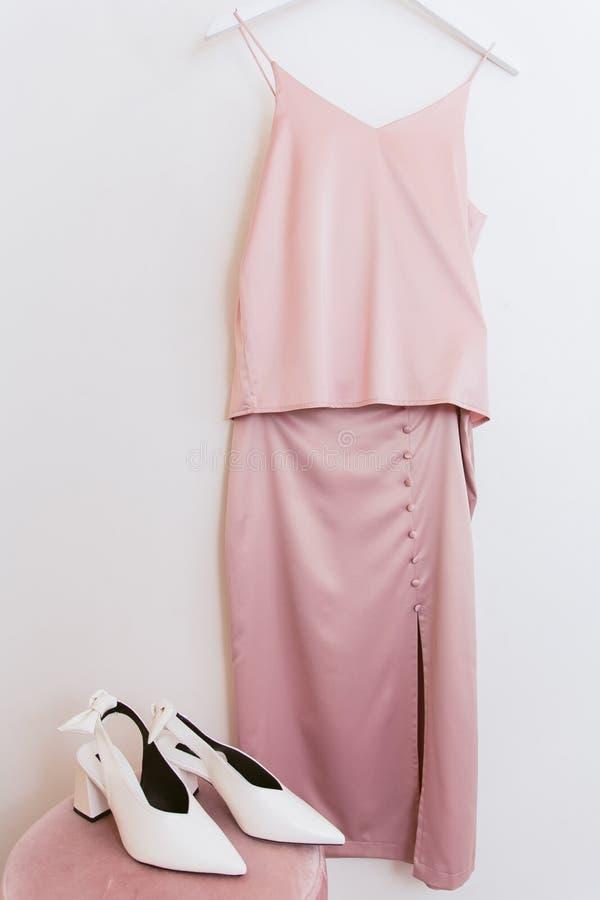Rosa Seidenbluse und Rock auf einem Aufhänger in der Umkleidekabine und weißen Schuhen auf dem Puff Kleidung und Kleidung im Umkl lizenzfreie stockbilder
