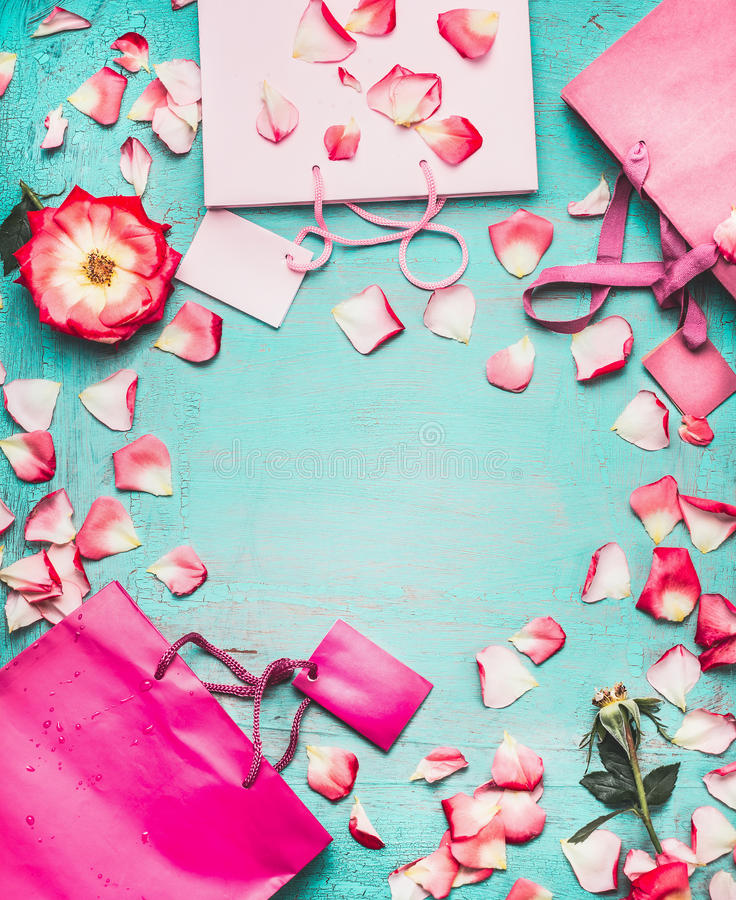 Rosa shoppingpåsar, blommor och mellanrumsetiketter på turkosbakgrund, bästa sikt royaltyfria foton