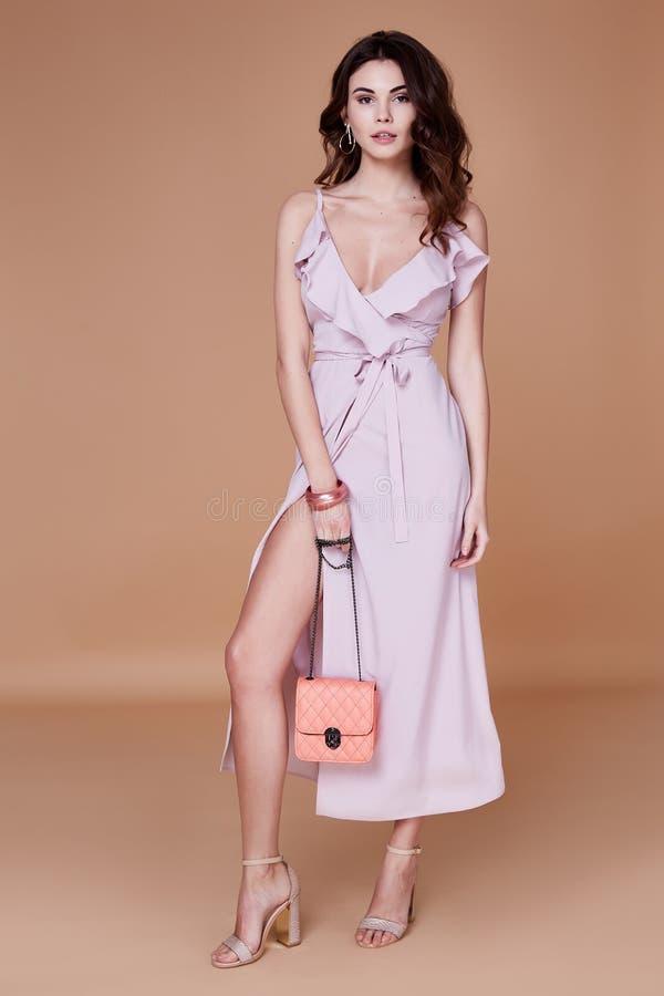 Rosa siden- klänning för sexiga för skönhetkvinna nätta för framsida för solbränna kläder för hud länge arkivbild