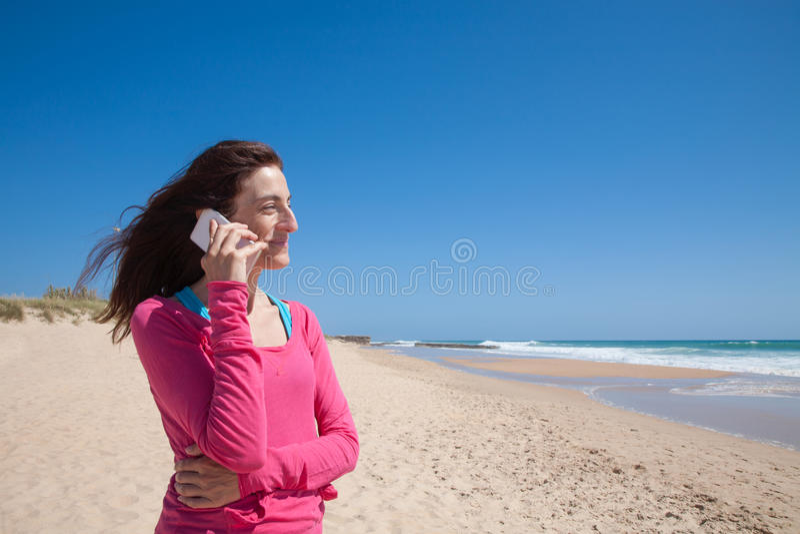 Rosa skjortakvinna som talar på mobil på stranden royaltyfri foto