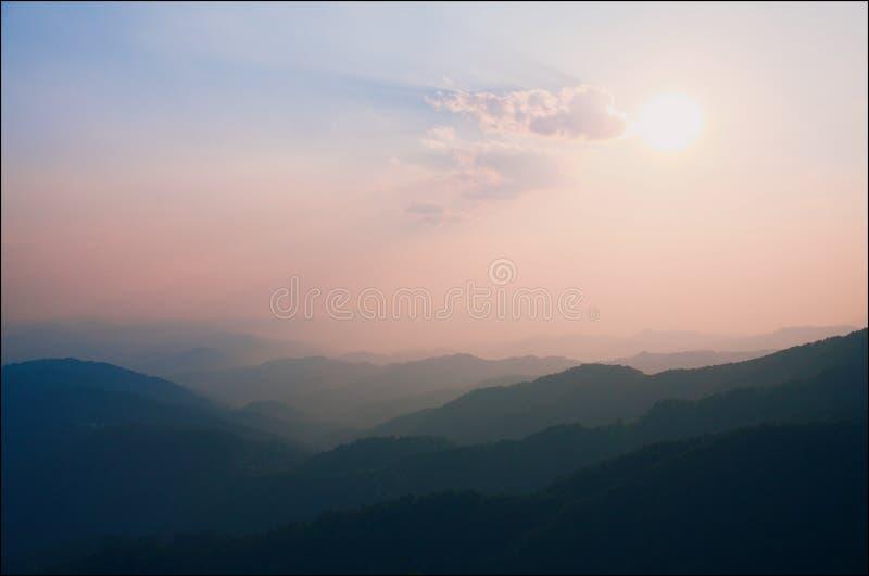 Rosa skuggor av solnedgången över bergen arkivfoto