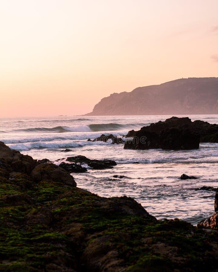 Rosa solnedgånghimmel, det härliga havet, sand och grönt vaggar Portuese strand arkivfoto