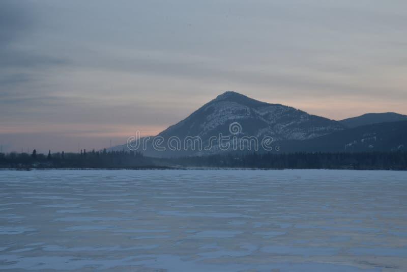 Rosa Sonnenaufgang über einer schneebedeckten Bergspitze mit gefrorenem See in lizenzfreies stockfoto