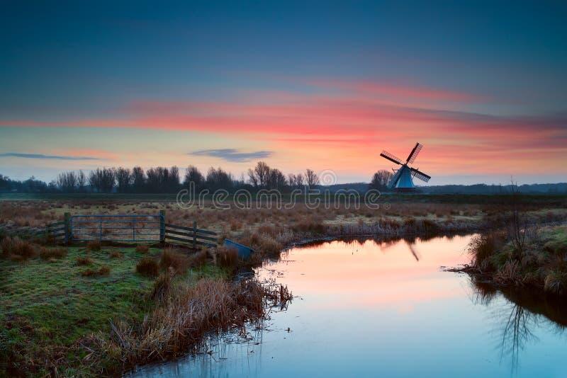 Rosa Sonnenaufgang über niederländischer Windmühle und Fluss lizenzfreies stockfoto