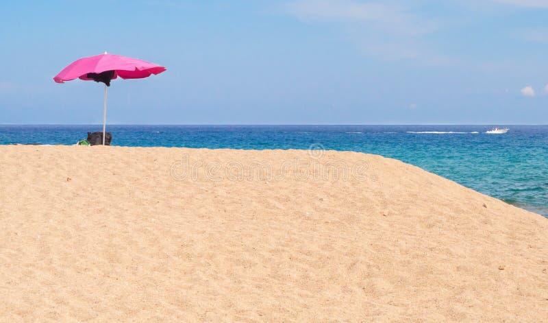 Rosa Sonnenschirm auf einem Strand lizenzfreie stockfotografie