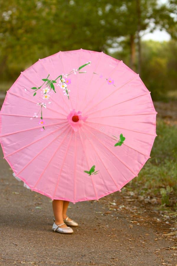 Rosa Sonnenschirm mit den Beinen und den Füßen des kleinen Mädchens, die von hinten darstellen stockfotos