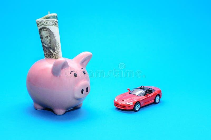 Rosa spargris med en bil på tabellen tonat Begrepp av sparande finanser och bidrag till egenskapen royaltyfri bild