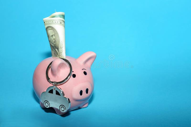 Rosa spargris med en bil på tabellen tonat Begrepp av sparande finanser och bidrag till egenskapen arkivfoto