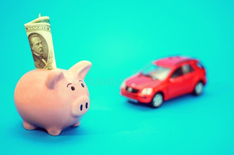 Rosa spargris med en bil på tabellen tonat Begrepp av sparande finanser och bidrag till egenskapen royaltyfria bilder