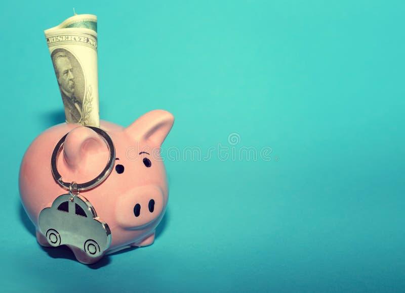 Rosa spargris med en bil på tabellen tonat Begrepp av sparande finanser och bidrag till egenskapen arkivbild