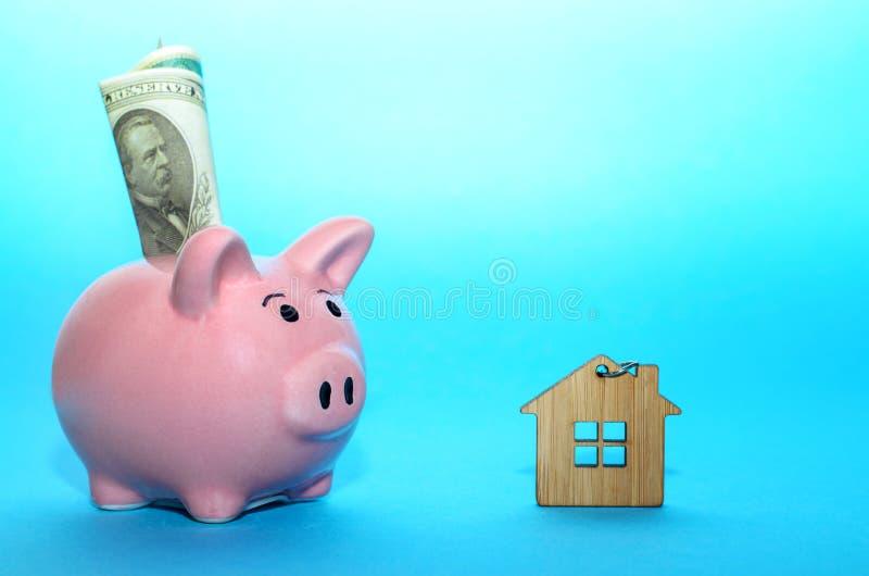 Rosa spargris med ett hus på tabellen tonat Begrepp av sparande finanser och fastighetinsättningar arkivbilder