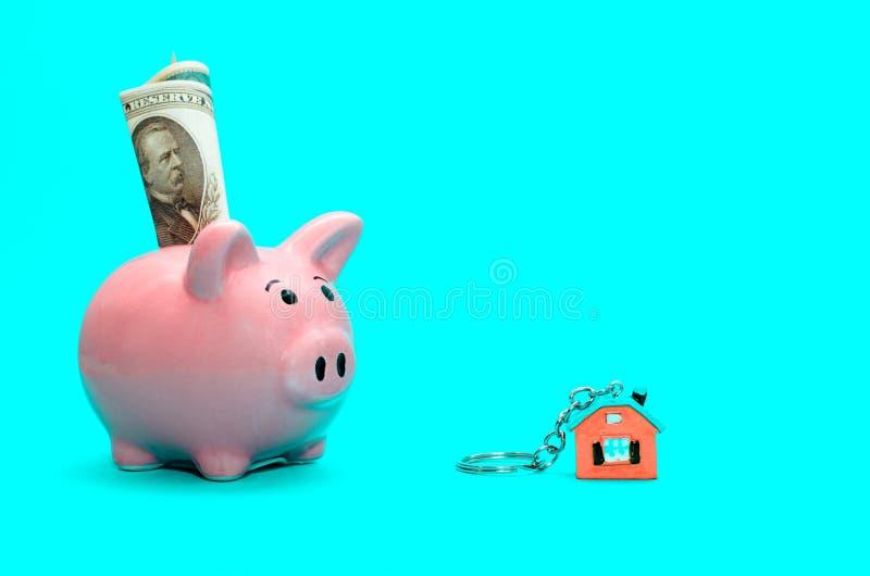 Rosa spargris med ett hus på tabellen tonat Begrepp av sparande finanser och fastighetinsättningar arkivfoto
