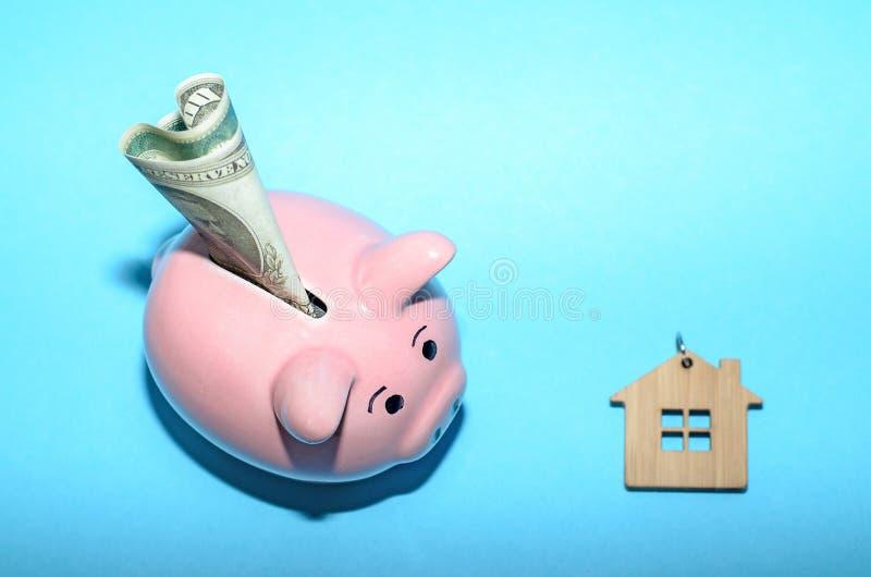 Rosa spargris med ett hus på tabellen tonat Begrepp av sparande finanser och fastighetinsättningar arkivfoton