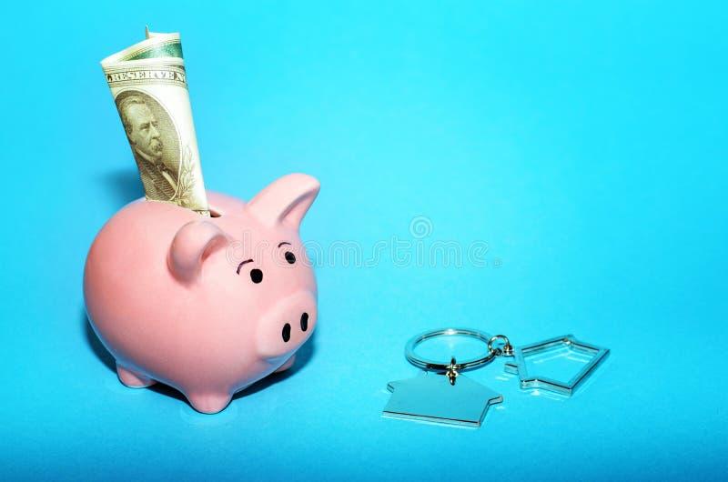 Rosa spargris med ett hus på tabellen tonat Begrepp av sparande finanser och fastighetinsättningar royaltyfria foton