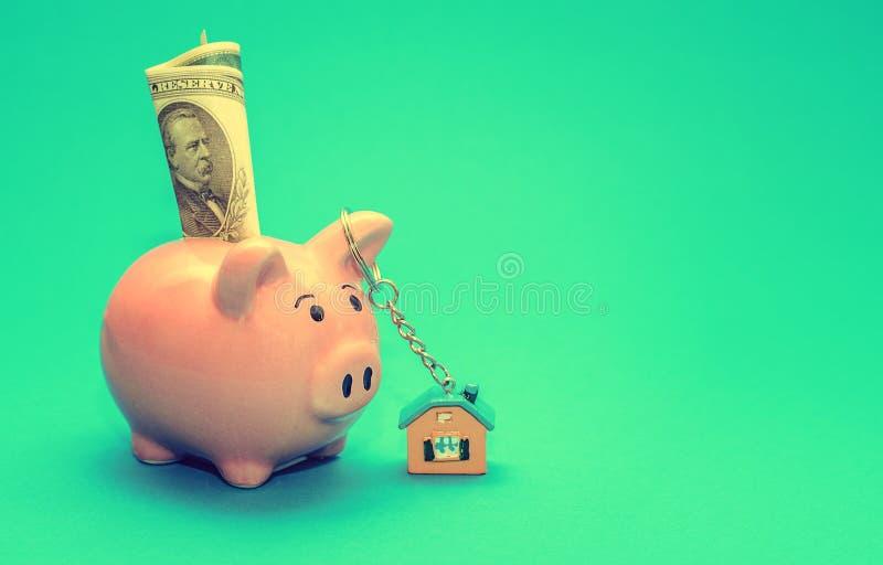 Rosa spargris med ett hus på tabellen tonat Begrepp av sparande finanser och fastighetinsättningar arkivbild