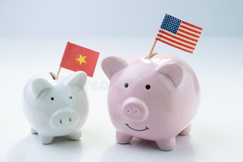 Rosa spargris med USA nationsflaggaanseende med liten vit med den Kina flaggan på vit bakgrund, metaforen av USA och Kina royaltyfri bild