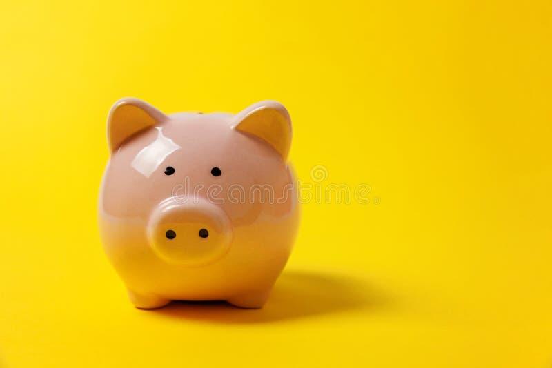 Rosa Sparschwein auf gelbem Hintergrund lizenzfreie stockbilder