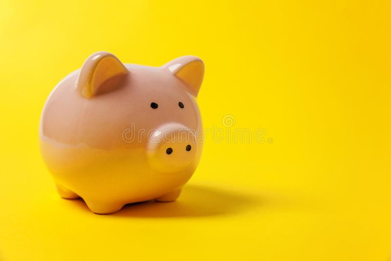 Rosa Sparschwein lokalisiert auf gelbem Hintergrund lizenzfreies stockbild