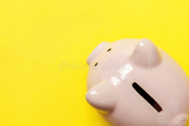 Rosa Sparschwein lokalisiert auf gelbem Hintergrund lizenzfreie stockbilder