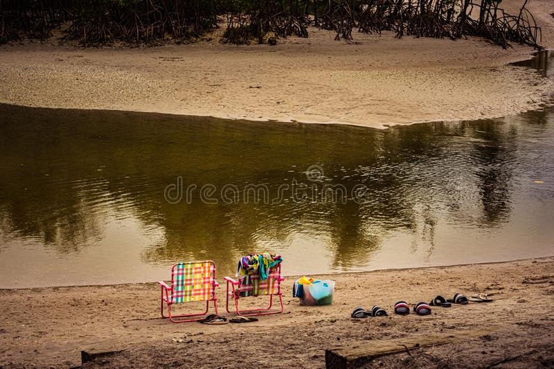 Rosa Stühle, bunte Tücher u. Strand-Spielwaren stockfoto