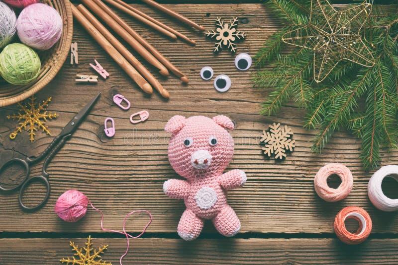 Rosa svin, symbol av 2019 lyckligt nytt år Virka leksaken för barn På tabellen dragar, visare, kroken, bomullsgarn Handgjorda han fotografering för bildbyråer
