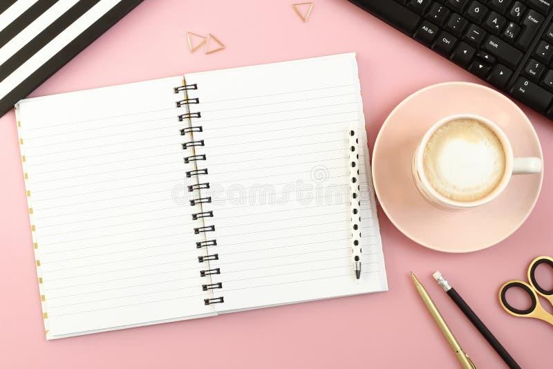 Rosa tabell för kontorsskrivbord med den öppna anteckningsboken, koppen kaffe, pennan, blyertspennan, sax och datoren royaltyfri fotografi