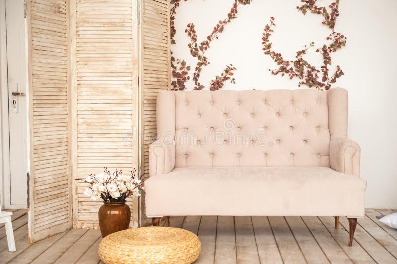 Rosa tappningsoffa och skärm i lantlig stil Inre av en ljus skandinavisk vardagsrum med blommor på väggen arkivfoton