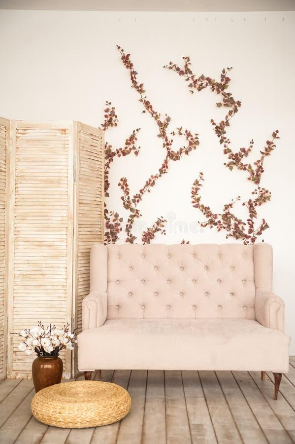 Rosa tappningsoffa och skärm i lantlig stil Inre av en ljus skandinavisk vardagsrum med blommor på väggen royaltyfria bilder